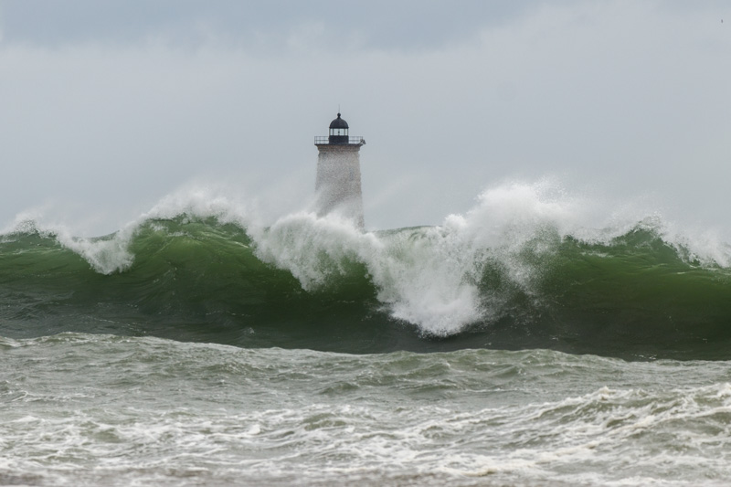 A wave crests in front of Whaleback Lighthouse