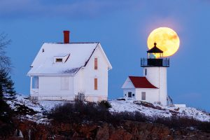 The full moon rises behind the Curtis Island Lighthouse