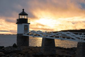 Golden light dances on the clouds behind Marshall Point Lighthouse.