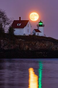 A full moon rising over Curtis Island Lighthouse.